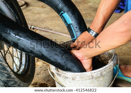 Technicians are investigating the leak of a motorcycle tire to repair. - stock photo