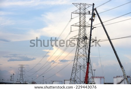 Technicians working on an electricity pole in the light of evening. - stock photo