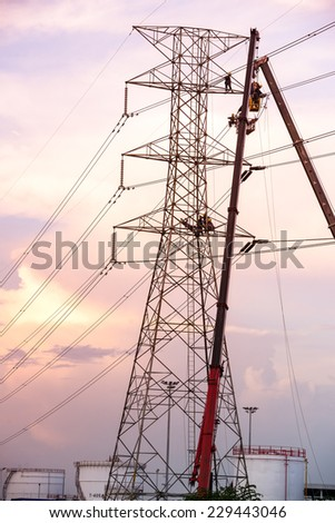 Technicians working on electricity pole in the light of evening. - stock photo