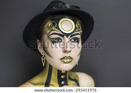 Techno golden girl with bright makeup. Streams of gold, shiny cheeks, black steam punk hat, big circle on forehead, body art. Sexy lips, decorations, accessories. Professional photo, new stylish idea - stock photo