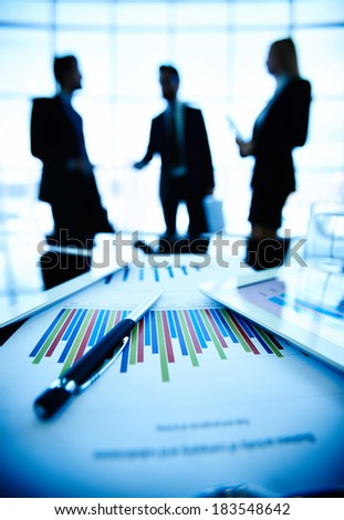 Technological devices and financial document with pen at workplace on background of three business partners communicating - stock photo