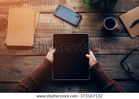 Technologies make life easier. Close-up top view image of woman holding digital tablet with copy space while sitting at the rough wooden table  - stock photo