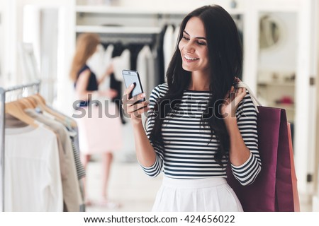 Technologies make shopping easier. Beautiful young woman with shopping bags using her smart phone with smile while standing at the clothing store  - stock photo
