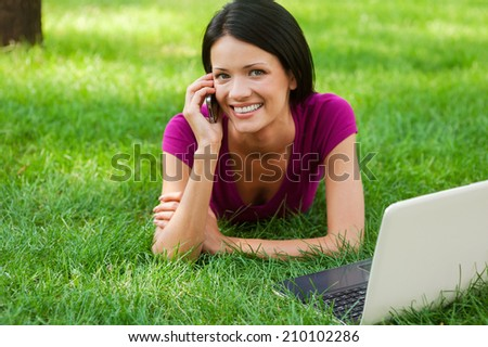 Technologies making life easier. Attractive young woman talking on the mobile phone and smiling while lying in grass with laptop laying near her - stock photo