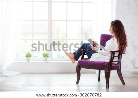 Technology and coziness. Beautiful young woman using tablet computer while sitting at armchair at home. - stock photo