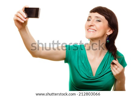 Technology and internet concept - smiling woman taking self picture with smartphone camera isolated - stock photo