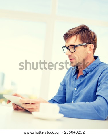 technology and lifestyle, distance learning concept - handsome man working with tablet pc and cup of coffee at home - stock photo