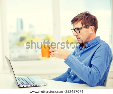 technology, business and lifestyle concept - man in eyeglasses working with laptop at home, holding a cup of warm tea or coffee - stock photo