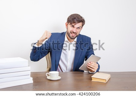 Technology, business concept - handsome man with beard and brown hair and blue suit and tablet pc computer and some books sitting in the office angry and unhappy.  Isolated on white background.   - stock photo