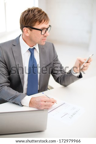 technology, business, internet and office concept - handsome businessman working with laptop computer and smartphone - stock photo