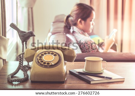 Technology change concept, young woman use smartphone near old telephone on wooden table - stock photo