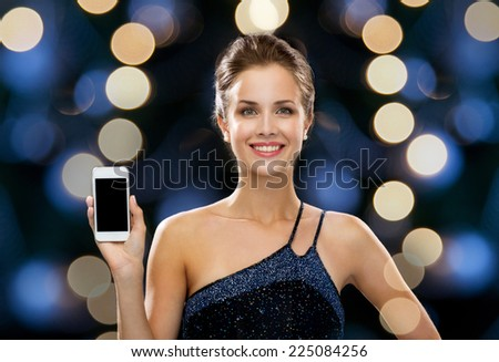 technology, communication, holidays, advertising and people concept - smiling woman in evening dress holding smartphone over night lights background - stock photo