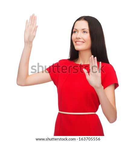 technology concept - attractive young woman in red dress working with virtual screen