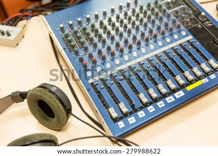 technology, electronics and equipment concept - control panel and headphones at recording studio or radio station - stock photo