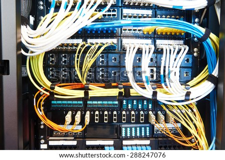 technology equipment with optical fibre cables connected to rack servers in room - stock photo