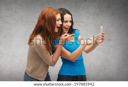 technology, friendship and people concept - two smiling teenagers pointing finger at smartphone - stock photo