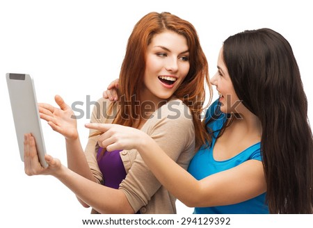 technology, friendship and people concept - two smiling teenagers pointing finger at tablet pc screen - stock photo