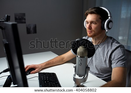 technology, gaming, entertainment, let's play and people concept - young man in headset with pc computer playing game at home and streaming playthrough or walkthrough video - stock photo