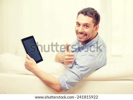 technology, home and lifestyle concept - smiling man working with tablet pc computer at home showing thumbs up - stock photo