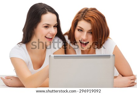 technology, internet and entertainment concept - two smiling teenage girls in white t-shirts with laptop computer - stock photo