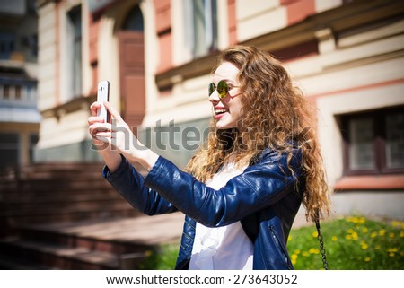 Technology internet and happy people concept - beautiful girl in sunglasses taking picture with smartphone camera, woman using cell phone. Urban style. - stock photo
