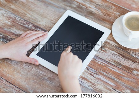 technology, internet and home concept - close up of female pointing finger to black blank tablet pc computer screen - stock photo