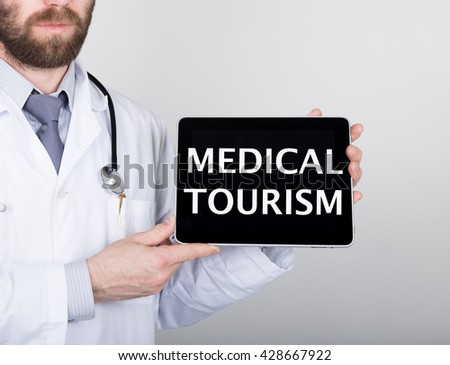 technology, internet and networking in medicine concept - Doctor holding a tablet pc with medical tourism sign. Internet technologies in medicine and tourism - stock photo