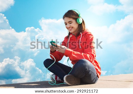 technology, lifestyle and people concept - smiling young woman or teenage girl with smartphone and headphones listening to music over blue sky and clouds background - stock photo