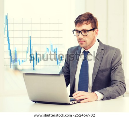 technology, money, business and office concept - handsome businessman in black eyeglasses with laptop computer and forex chart - stock photo