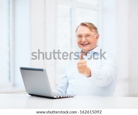 technology, oldness and lifestyle concept - old man in eyeglasses with laptop computer at home showing thumbs up - stock photo