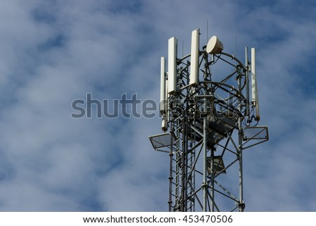 Technology on the top of the GSM (4G) tower (antenna, transmitter), blue sky, white clouds. - stock photo