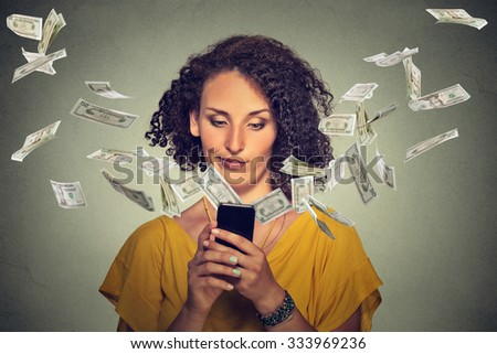 Technology online banking money transfer e-commerce concept. Annoyed young woman using smartphone with dollar bills flying away from screen isolated gray wall office background. Human face expression  - stock photo