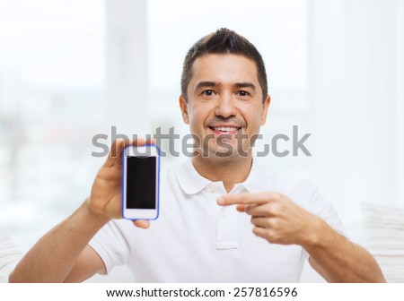 technology, people, lifestyle and communication concept - happy man showing smartphone black blank screen at home - stock photo