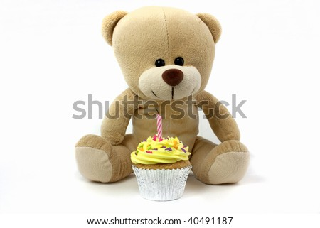 teddy and cupcake with 1 candle on white - stock photo