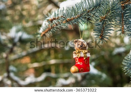 Teddy bear and red sock, Christmas toy on a Christmas tree under snow