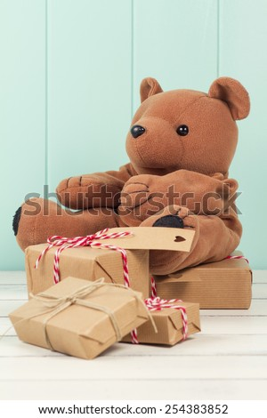 Teddy bear and some paper parcels wrapped tied with tags. Christmas gift boxes on a white wooden table. Vintage Style. - stock photo
