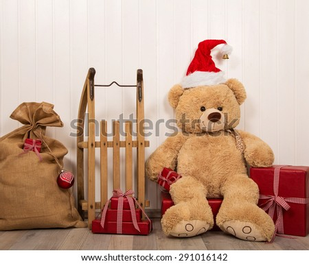 Teddy bear as a santa with an old wooden sleigh and red christmas presents. - stock photo
