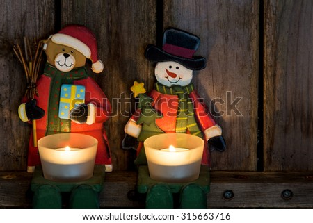 Teddy bear as santa claus  and snow man with candles - stock photo