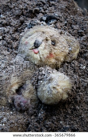 Teddy bear buried in a pile of ash - stock photo