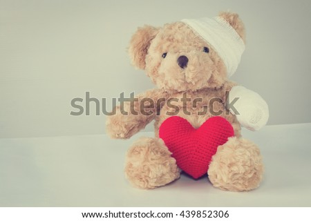 Teddy bear have an accident bandaged head and arm. with red heart yarn front side. copy space vintage style. - stock photo
