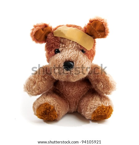Teddy bear hurt with plaster on his head over a white background - stock photo