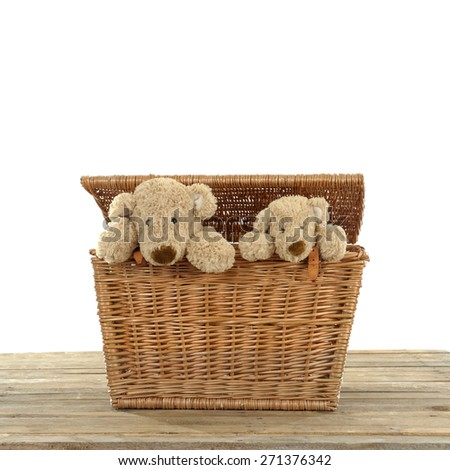 Teddy bear in a wicker trunk - stock photo