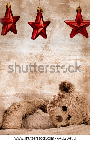 teddy bear in blanket under three Christmas red stars on grunge background with copy space - generic toy with slightly modified appearance - stock photo