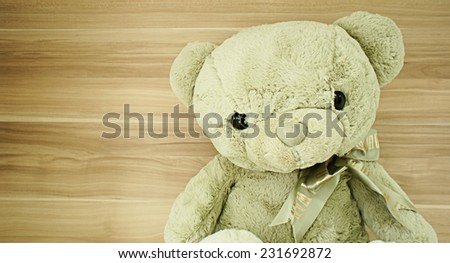 Teddy bear in front of wooden wall, in retro style - stock photo