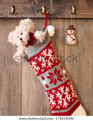 Teddy bear in knitted Christmas stocking with hanging snowman decoration - stock photo