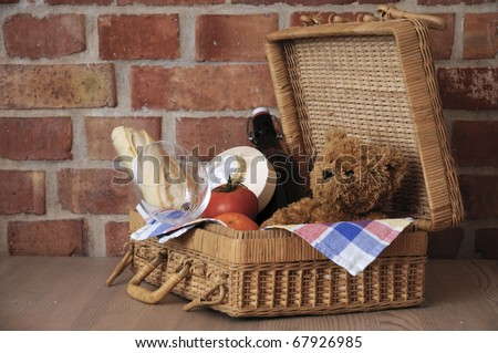 Teddy bear in picnic basket and snacks.