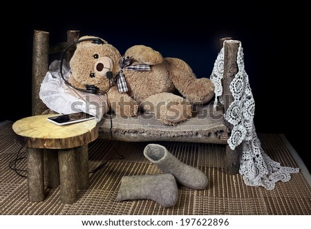 Teddy bear in the headphones with a mobile phone is resting in bed on a black background - stock photo