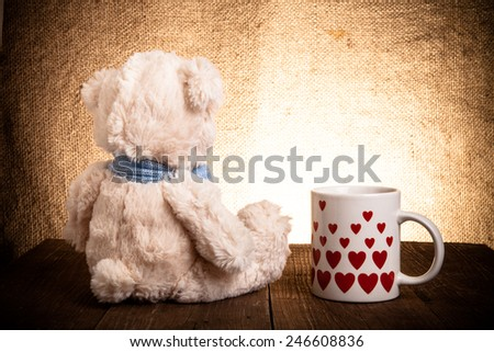 Teddy bear is sitting on the old wooden table. Mug with hearts.