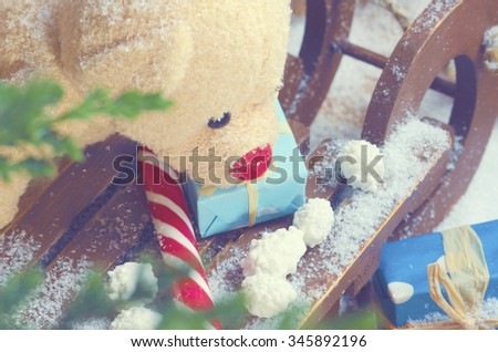 Teddy bear on a Christmas sleigh with candy cane and presents. Selective focus - stock photo