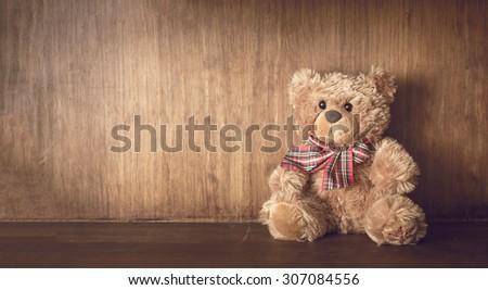 Teddy bear on a wooden shelf - stock photo
